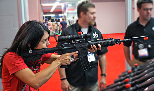 Top Shot's Gabby Franco tries out a scope at the NRA Convention in St. Louis, Missouri.