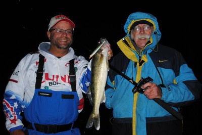 Mark Martin holds a walleye that Eric Sharp, right, caught on Muskegon Lake.