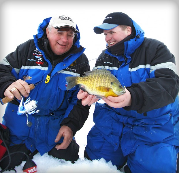 "The fishing world mourns the loss of Jim Hudson, shown here smiling with Dave Genz. Whether they were working together or fishing for fun, Genz was extremely impressed by Hudson's capabilities and personality. ""He was headed,"" says Genz, ""to the top of the ice fishing industry."""