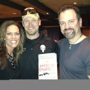"Chris Kyle signs a copy of ""American Sniper"" for Jana Waller and Jim Kinsey of Skull Bound TV."