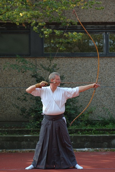 A man practicing a kyudo shot.