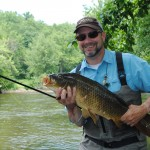 Dirk Fischbach shows off a Huron River carp.