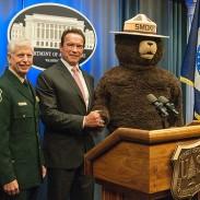 Arnold Schwarzenegger shakes hands with Smokey the Bear alongside Chief Tom Tidwell (far left).
