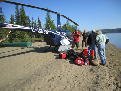 The anglers stand around their helicopter with gear piled up.
