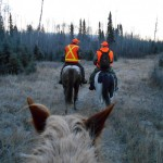 Guide Pat Bergson, left, and hunter Jim Parks of Missouri ride a trail into the Duck Mountain Provincial Forest.