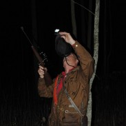 Jim Zimmerman shines his headlamp at a treed raccoon so he can shoot it.