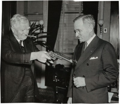 John Nance Garner (left) shows the James revolver and another firearm to Harry Truman.