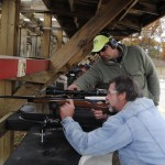 Alex Koptyev adjusts the crosshairs on the scope of Alex Webster's 7mm Magnum to where the bullet hit.