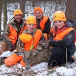 As mentors Ben Gruber (l rear) and Tyler Franks look on, Sam (holding deer) and Isaac Brewer show off Sam's first deer, an 8-point buck, taken on Dec. 14 during a Kids And Mentors Outdoors deer hunt held at MacKenzie Environmental Education Center near Poynette.