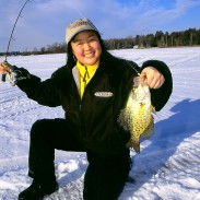 Kristi Takasaki with a beautiful crappie caught in bright sunshine, but with a glow jig! Image by Ted Takasaki.