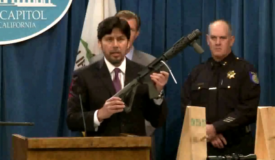 Senator Kevin de Leon holds up a self-assembled rifle, one of the many that the new legislation could affect.