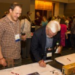 Auction co-chairman Tony Bynum and POMA media member Tim Flanigan enjoy bidding during the POMA conference silent auction.