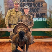 NWTF hunt winner Ian Shofner (right), and guide Joel Pile (left), pose with their turkey taken at the Kansas Governor's One Shot Turkey Hunt.