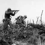 In this iconic image from World War II, a United States Marine (standing) fires a Thompson submachine gun.
