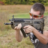 Bullpups, like the Tavor the author is holding in this image, can present some unique challenges to 3-gun shooter more accustomed to ARs. Image by Oleg Volk.