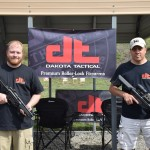 Joe Stoppiello (right) stands in front of his company's banner at the Ninth Combat Rifle Championship. Stoppiello is holding a D300P, while his employee Mike (left) holds a D54P.