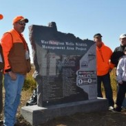 Local supporters gather around a granite monument placed on the new Worthington Wells tract of the Lake Bella Wildlife Management Area.  The 147-acre tract, 6 miles southwest of Worthington, provides valuable wildlife habitat and helps protect water from pollutants in the center of Worthington's municipal water supply.