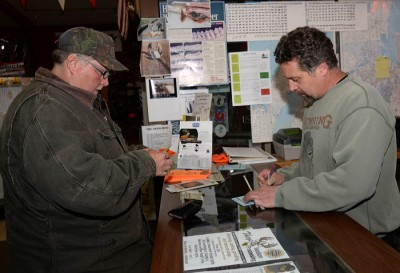 Lee Simonar, right, owner of Lee's Sports in Luxemburg, Wisconsin, processes deer-registration paperwork for Dana Lemens, Luxemburg, who arrowed this buck November 9 during archery season.