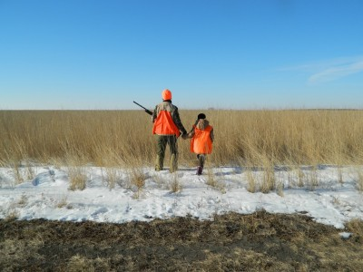 "In this photo from day three of the author's SoDak pheasant hunt, Jodi and Sophie Stemler ""block,"" a method used to keep birds from flying out of the opposite end of a field as hunters walk through it."