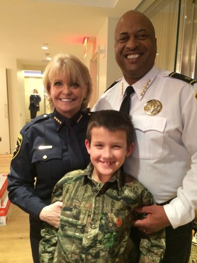 Sheriff Carolyn Welsh of Chester County, PA (left) and Sheriff Alex Underwood of Chester County, SC (right) stand smiling over Alex Collins (center) on his first hunting trip.