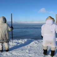 Two hunters on the shore of the Belcher Islands look out towards the water, where a pod of beluga whales is trapped in the ice. The region is well known for its frigid temperatures, and its unforgiving nature.