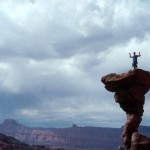A climber stands on top of The Cobra in Moab, Utah.