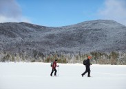 Snowshoers cross a frozen Lonesome Lake.